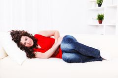 Girl on the sofa with stomach ache Royalty Free Stock Photos