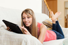 Girl on sofa with tablet pc Stock Photos