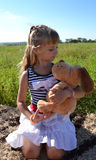 girl with soft dog toy plays in the meadow Stock Images