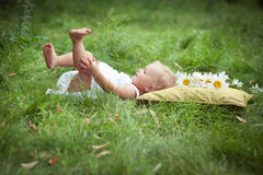 Girl on soft pillow in fresh spring grass Royalty Free Stock Photography