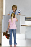 Girl (7-9), with soft toy, talking to female check-in attendant at airport check-in area, woman holding boarding passes, smiling,  Stock Photo