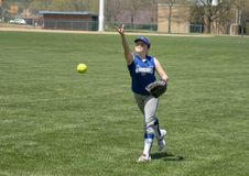 Girl softball pitcher warming up before a game. Pictured is an eleven yearold caucasian girl warming up her softball pitching before a game. She is on green royalty free stock image
