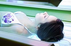 Girl is in a solarium. Young woman is tanning in solarium Royalty Free Stock Images