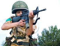 Girl soldier. British girl soldier in desert uniform aiming her rifle stock photography