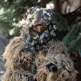 Girl soldier in ghillie camouflage. Young girl soldier defender with blue eyes face closed by mask in ghillie camouflage military ammunition with gun standing on Royalty Free Stock Image