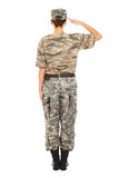 Girl - soldier in the military uniform. Young girl-soldier in the camouflage military uniform and hat greets someone, standing by back Royalty Free Stock Photo