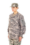 Girl - soldier in the military uniform. Young girl-soldier in the camouflage military uniform and hat stands by the front Royalty Free Stock Image
