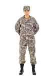 Girl - soldier in the military uniform. Young girl-soldier in the camouflage military uniform and hat stands by the front, hands behind the back Royalty Free Stock Photography