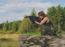 Girl soldiers take aim from the gun being on a hill Royalty Free Stock Photo