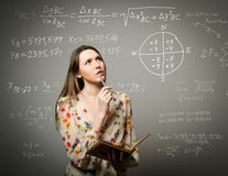 Girl solving equation. Thoughtful girl holding pen and documents and solving equation royalty free stock images