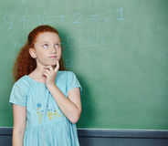 Girl solving math problem in school. Pensive girl solving math problem in elementary school class Royalty Free Stock Photos