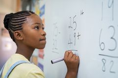 Girl solving mathematical addition. Portrait of african girl writing solution of sums on white board at school. Black schoolgirl solving addition sum on white stock photos