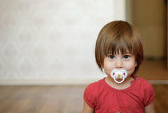 Girl with a soother in her mouth. Litttle girl with a soother in her mouth Royalty Free Stock Photography