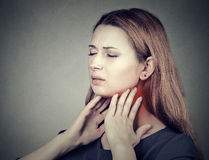 Girl with sore throat neck colored in red. Sick woman having pain in throat. Closeup side profile girl with sore throat touching her neck colored in red. Sick Stock Photo