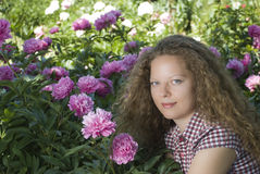 Girl sorrounded by peonies Royalty Free Stock Image