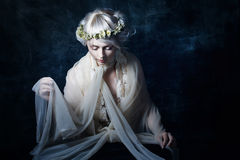The girl in sorrow. Beautiful sad girl with a wreath on his head Royalty Free Stock Image