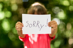 Girl with Sorry sign. Blurred girl holding a piece of paper with the word Sorry in front of her royalty free stock photo
