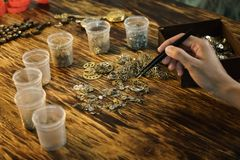 Woman watchmaker works at wooden table royalty free stock photo