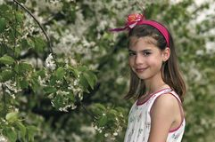 Girl in the sour cherry orchard by tree Royalty Free Stock Photo