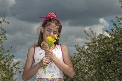 Girl in the sour cherry orchard with yellow flower Stock Images