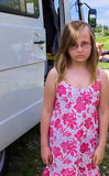 Girl with a sour face on the background of the bus. Unhappy girl of the European appearance for about nine years in nature, stands near the bus behind the child Royalty Free Stock Image
