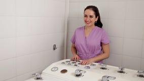 Girl Spa de salonarbeider regelt de stroom van water in de hete ton stock video