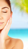 Girl on spa resort. Picture of cute brunette girl with closed eyes enjoying tropical nature, woman tanning on the beach, half face, skin care, natural makeup Royalty Free Stock Photo