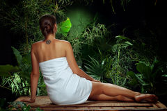 Girl in spa. View of nice young woman meditating in spa tropic environment Royalty Free Stock Image