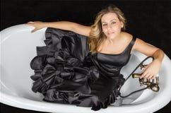 Girl with spanish flamenco dress in a bathtub. Portrait of beautiful fashion girl with black spanish flamenco dress posing in a vintage bathtub Royalty Free Stock Photo