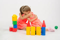 Girl spared another girl. The four-year and six-year old girl playing in a European-style cubes, isolated on a light background Stock Photo