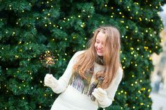 Girl with a sparkler near brightly Christmas tree Stock Images