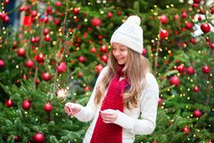 Girl with a sparkler near brightly Christmas tree Royalty Free Stock Image