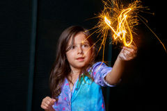 Girl With Sparkler. A girl in pajamas holds a burning sparkler up in the air while looking at it with wide eyes Royalty Free Stock Image