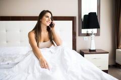 Girl speak phone in the bed. Beautiful girl speak phone in the bed Stock Photo