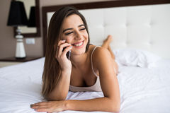 Girl speak phone in the bed. Beautiful girl speak phone in the bed Royalty Free Stock Images