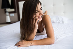 Girl speak phone in the bed. Beautiful girl speak phone in the bed Royalty Free Stock Photos