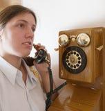 Girl speak by retro wooden phone Stock Photo