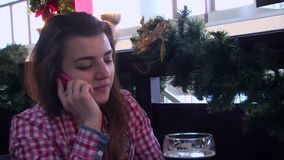 Girl speaking by cell phone and drinking beer at a restaurant table stock video
