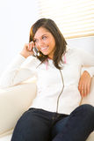 Girl speaking by cellphone. A girl sitting on couch. She's speaking by cellphone and smiling Stock Photo