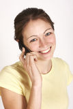 Girl speaking on mobile phone. Smiling Girl with yellow shirt speaks on phone Stock Image