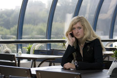 The girl speaking by phone. The blond young girl speaking by phone Royalty Free Stock Photo