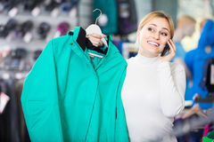 Girl  speaking on the phone and choosing a sport jacket Stock Images
