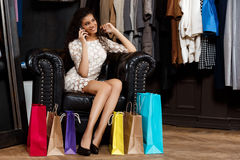 Girl speaking on phone, sitting in shopping mall with buyings. Young beautiful african girl speaking on phone, smiling, sitting in shopping mall with buyings royalty free stock photo