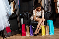 Girl speaking on phone, sitting in shopping mall with buyings. Young beautiful african girl speaking on phone, smiling, sitting in shopping mall with buyings stock image
