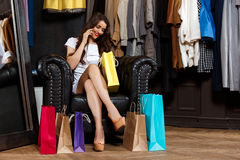 Girl speaking on phone, sitting in shopping mall with buyings. Young beautiful girl speaking on phone, smiling, sitting in shopping mall with buyings royalty free stock image