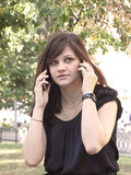 Girl speaking on two mobile phones. Portrait of girl speaking on two mobile phones Royalty Free Stock Image