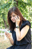 Girl speaking on two mobile phones Stock Photos