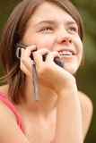 Girl speaks on cellular telephone. Young charming girl talks by mobile phone and laughs Stock Photo