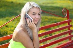 Girl speaks by  mobile phone. Summer day, park Stock Photos