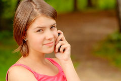 Girl speaks by mobile phone. The young beautiful girl talks on a cellular telephone in city park Royalty Free Stock Image